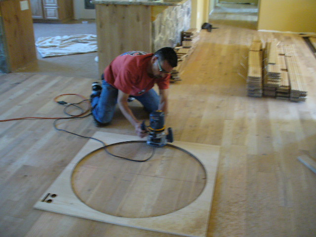 Man cutting out a circle in the wood floors