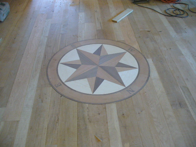 Circle filled in with compass design composted of different color wood flooring pieces